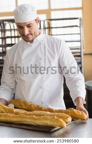 Baker looking at freshly baked baguettes in the kitchen of the bakery - stock photo