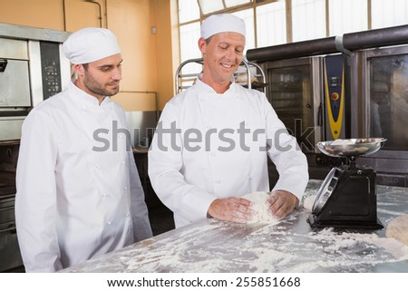 Baker looking his colleague kneading dough in the kitchen of the bakery - stock photo