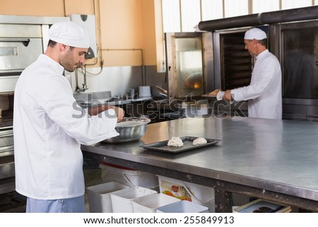 Baker making dough in mixing bowl in the kitchen of the bakery