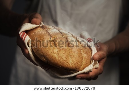 Baker man holding a warm bread - stock photo
