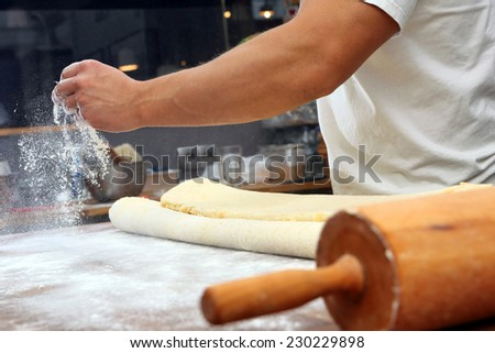 Baker poured flour on the table for rolling dough