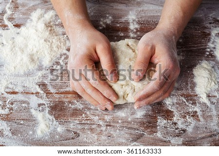 Baker prepares the dough on a wooden table, male hands knead the dough with flour, homemade pastry for bread or pizza, top view, vintage style