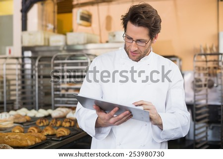 Baker reading something on clipboard in the kitchen of the bakery - stock photo