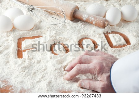 "Baker's hand and word ""FOOD"" written in a flour - stock photo"