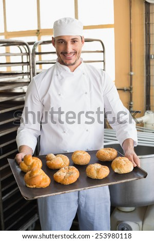Baker showing tray of rolls in the kitchen of the bakery - stock photo