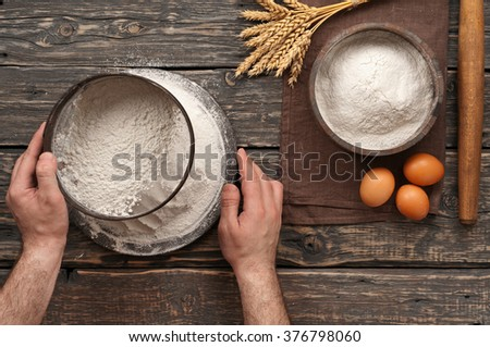 baker sift the flour on a dark rustic wooden background in a bakery. Top view with copy space - stock photo