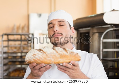 Baker smelling freshly baked loaf in the kitchen of the bakery - stock photo