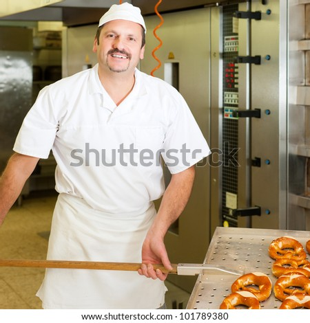 baker standing in his bakery in the morning and is baking bread or buns - stock photo