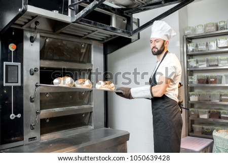 Baker taking off baked breads with shovel from the professional oven at the manufacturing