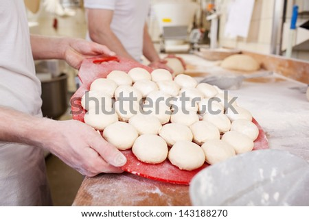 Baker with a tray of unbaked rolls packed ready to go into the oven for baking - stock photo