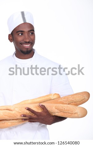 Baker with an armful of baguettes - stock photo