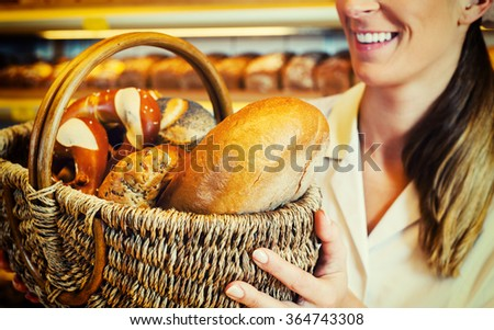 Baker woman in backer selling bread in basket, filtered image - stock photo