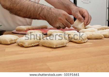 Baker working with fresh dough - stock photo