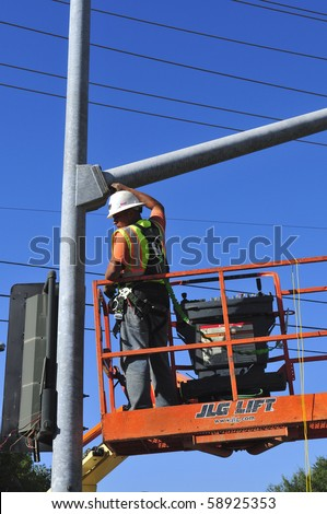 BAKERSFIELD, CA - AUG 12: Electricians completely replace traffic signals, poles and mast arms at a major intersection on August 12, 2010, at Bakersfield, California. Mast arm is bolted to the pole. - stock photo