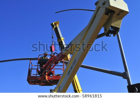 BAKERSFIELD, CA - AUG 12: Electricians completely replace traffic signals, poles and mast arms at a major intersection on August 12, 2010, at Bakersfield, California. Mast arm is positioned. - stock photo