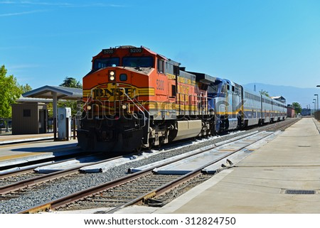 BAKERSFIELD, CA - AUGUST 29, 2015: A rare sight happens when a BNSF freight locomotive couples to an Amtrak passenger train. The Amtrak engine is disabled.