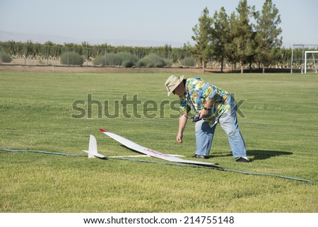 BAKERSFIELD, CA-AUGUST 24, 2014: George Gillburg retrieves his craft after a long thermal flight in the monthly contest hosted by the Southern San Joaquin Soaring Society. - stock photo
