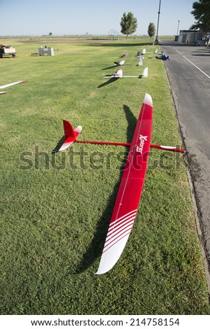 BAKERSFIELD, CA-AUGUST 24, 2014: Sleek radio controlled sailplanes rest on the grass, ready to fly in the monthly contest hosted by the Southern San Joaquin Soaring Society. - stock photo