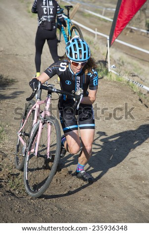 BAKERSFIELD, CA - DECEMBER 6, 2014: An unidentified woman contestant during the Hart Park Cyclocross rides as far up the hill as possible, then dismounts and pushes the bike. - stock photo