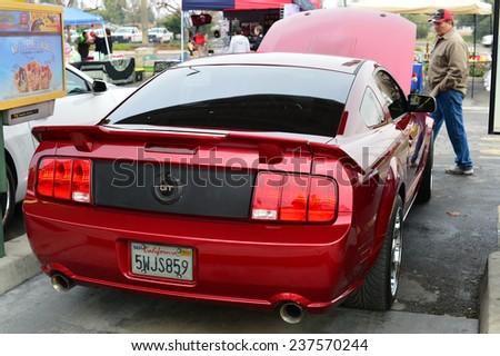 BAKERSFIELD, CA - DECEMBER 13, 2014:  Classic Ford Mustangs in various iterations have shown up to compete with the Chevys in the Christmas Joy Ride and Toy Run Car Show. - stock photo