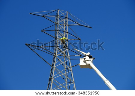 BAKERSFIELD, CA - DECEMBER 7, 2015: Electrician linemen work up high, aided by a crane, man lift and ground crew,  to disassemble a high voltage tower that is being replaced.