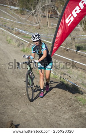 BAKERSFIELD, CA - DECEMBER 6, 2014: Women contestants must also carry their bikes up steep hills during the Hart Park Cyclocross, then mount up at the top, ready to race again. - stock photo