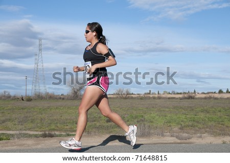 BAKERSFIELD, CA - FEB 19: The Bakersfield Track Club conducts the Half Marathon on February 19, 2011, at Bakersfield, California. Female contestant runs her own race apart from the group. - stock photo