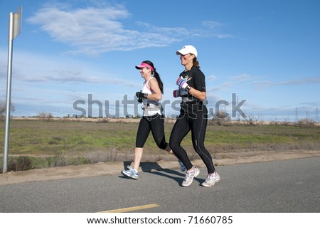 BAKERSFIELD, CA - FEB 19: The Bakersfield Track Club conducts the Half Marathon on February 19, 2011, at Bakersfield, California. Two women run together. - stock photo