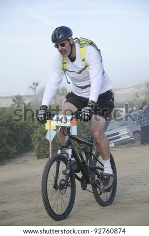 BAKERSFIELD, CA - JAN 14: An unidentified cyclist races along the dusty trail during the Rio Bravo Rumble biathlon (running and mountain biking) on January 14, 2012, in Bakersfield, California. - stock photo