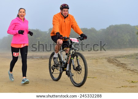 BAKERSFIELD, CA - JAN 17, 2015: An unidentified pair of contestants warm up in the fog for the Rio Bravo Rumble biathlon (running and mountain biking). - stock photo