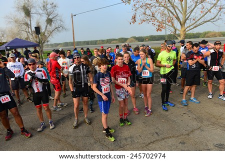 BAKERSFIELD, CA - JAN 17, 2015: Contestants line up at the start of the Rio Bravo Rumble running portion of the biathlon (running and mountain biking) under cold and foggy conditions. - stock photo