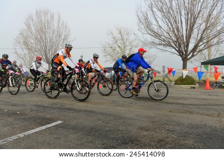 BAKERSFIELD, CA - JAN 17, 2015: Contestants race from the starting line of the Rio Bravo Rumble cycling portion of the biathlon (running and mountain biking) into extremely foggy conditions. - stock photo