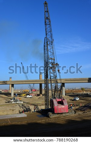 BAKERSFIELD, CA - JANUARY 5, 2018: A crane-supported pile driver goes deep into the earth to prepare for a concrete column for the Kern River Bridge Improvements Project.