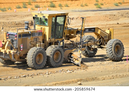 BAKERSFIELD, CA-JULY 18, 2014: Equipment with a blade is used to bring the road base to grade during the project to widen State Route 178.