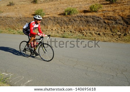 BAKERSFIELD, CA - JUN 1: An unidentified men's category rider is happy to crest a hill during the District Road Race Championships on June 1, 2013, at Bakersfield, California.