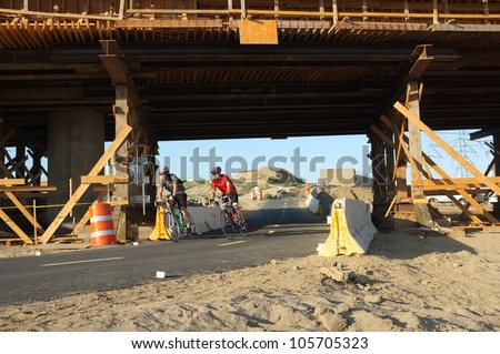 BAKERSFIELD, CA-JUN 21: Showing contrasting transportation modes, unidentified cyclists must temporarily use the detour under the Westside Parkway project on June 21, 2012, in Bakersfield, California.