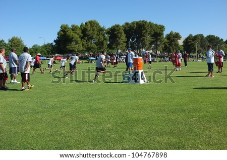 BAKERSFIELD, CA - JUNE 9: Boys sprint to get in shape for the Golden Empire Youth Football Camp at Bakersfield Community College on June 9, 2012,  in Bakersfield, California. - stock photo