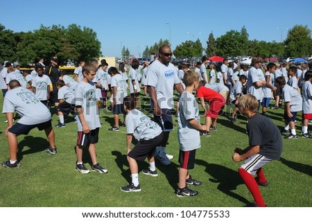 BAKERSFIELD, CA - JUNE 9: Coaches teach the fundamentals of the game to boys at the Golden Empire Youth Football Camp at Bakersfield Community College on June 9, 2012,  in Bakersfield, California.
