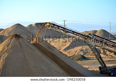 BAKERSFIELD, CA-JUNE 12, 2014: During the project to widen State Route 178 excavated material is crushed, then conveyed to a gigantic mound of road base. Material pours from the end of the conveyor.