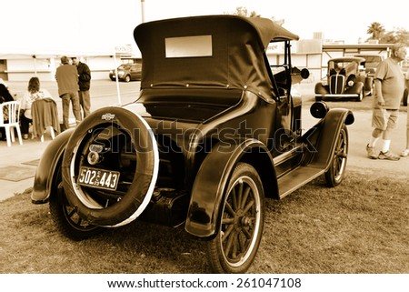 """BAKERSFIELD, CA - MARCH 14, 2015: James Pengilleu brings his immaculately prepared 1923 Chevrolet Roadster to display at the """"Cruisin' for a Wish"""" classic car show. Sepia toned image. - stock photo"""