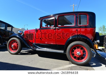 BAKERSFIELD, CA - MARCH 14, 2015: Members of the local Ford Model A club gather informally today to discuss their cars and socialize. This bright red 1930 four door sedan is a beauty. - stock photo