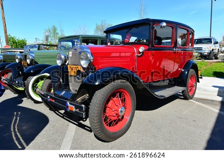BAKERSFIELD, CA - MARCH 14, 2015: Members of the local Ford Model A club gather informally today to discuss their cars and socialize. This bright red 1930 four door sedan is a beauty.