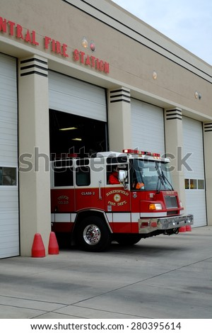 BAKERSFIELD, CA - MAY 21, 2015: A fire truck with firemen personnel departs the Central Fire Station after receiving a call. - stock photo