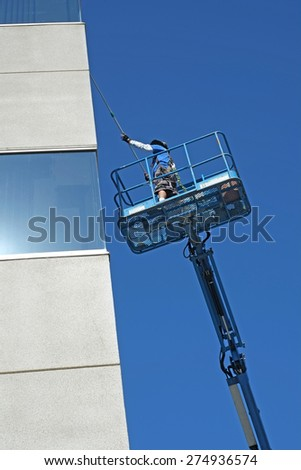 BAKERSFIELD, CA - MAY 2, 2015: A window washer works high off the ground on the platform of a man lift to wash the windows of a Kern County office building. - stock photo