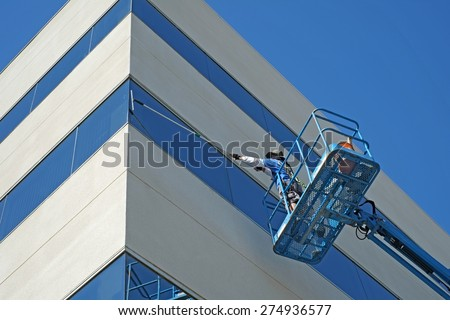 BAKERSFIELD, CA - MAY 2, 2015: Carlos Ruiz works high off the ground on the platform of a man lift to wash the windows of a Kern County office building.