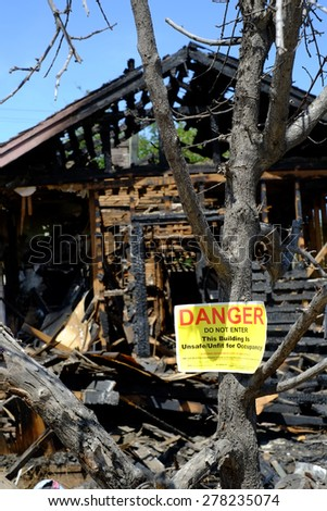 BAKERSFIELD, CA - MAY 14, 2015: The aftermath of a recent residential fire leaves this house charred and uninhabitable. Warning signs are posted by the city. (Selective focus on sign.)