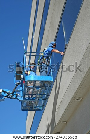 BAKERSFIELD, CA - MAY 2, 2015: Two unidentified window washers wash the windows of a Kern County office building. - stock photo