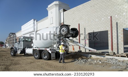 BAKERSFIELD, CA - NOVEMBER 22, 2014: During construction of the Shops at River Walk a transit mix truck is used to place concrete precisely where it's needed om the job.