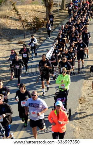 BAKERSFIELD, CA - NOVEMBER 7, 2015: Police academy cadets (dressed all in black) start together behind their banner for the 33rd Annual Bakersfield Police Department Memorial Run. - stock photo
