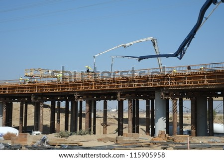 BAKERSFIELD, CA-OCT 16: Concrete pouring has begun on new bridge across the Kern River by pumping in flexible hoses supported by articulated cranes on October 16, 2012, in Bakersfield, California.